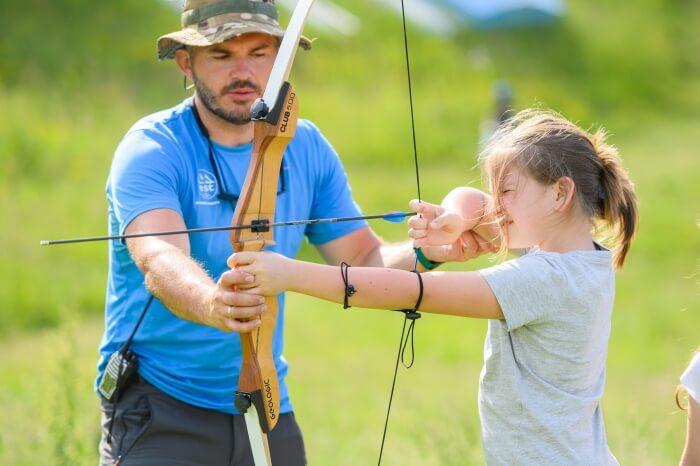 Avantura u prirodi za celu porodicu. Devojčica uči streličarstvo, da koristi luk i strelu.