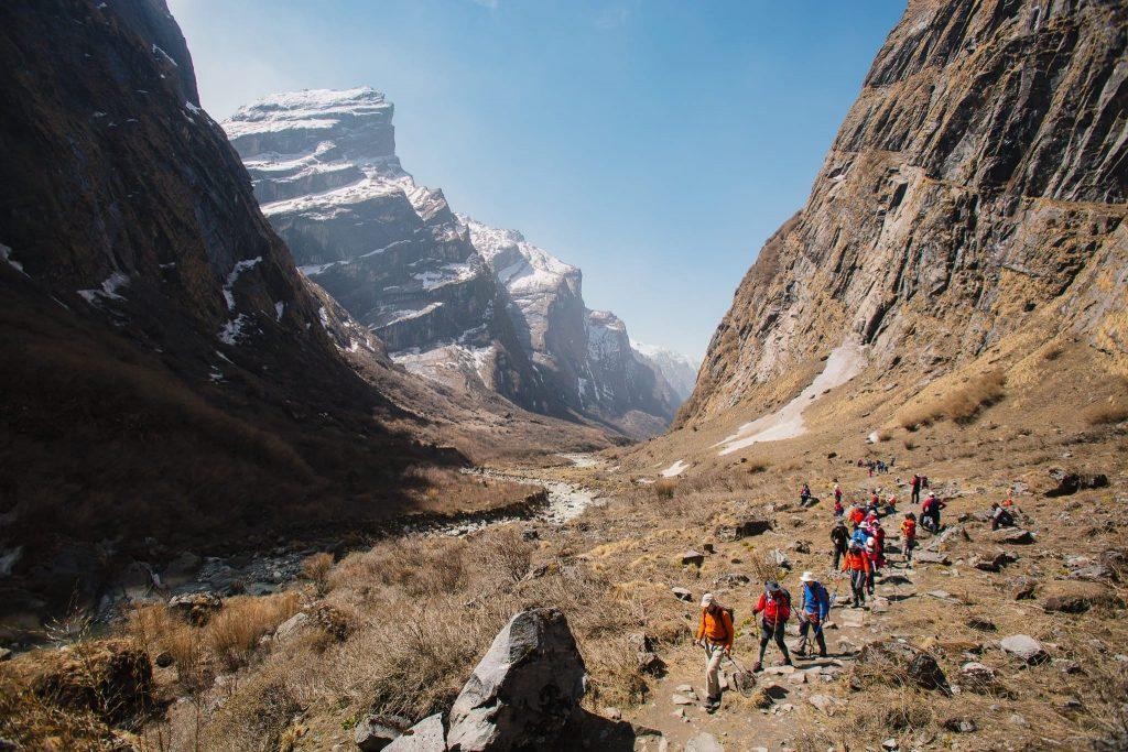 Grupa ljudi u koloni na planinarenju sa planinarskom opremom. Iza njih vide se planine.