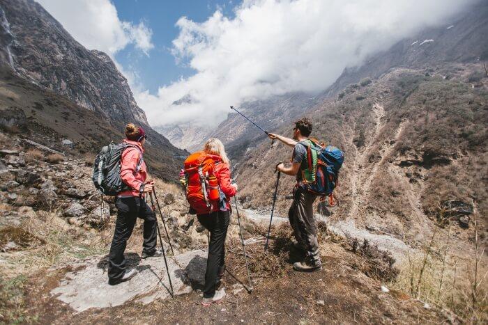 Troje planinara nose ranac za planinarenje na leđima i gledaju u planine ispred sebe.