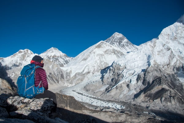 Planinar u Nepalu, sedi i gleda u snežne vrhove Himalaja.