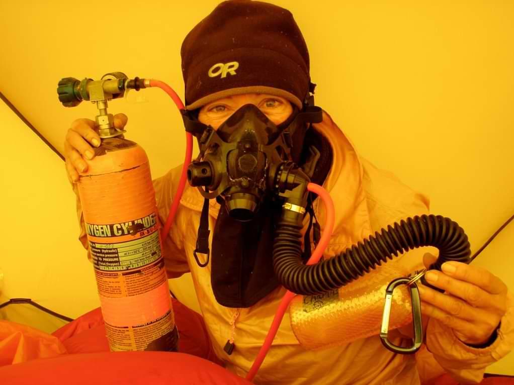 Alpinista u šatoru sa bocom kiseonika radi sprečavanja visinske bolesti.